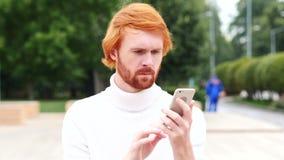 Usando el smartphone para en línea hojear, hombre con los pelos rojos, al aire libre almacen de metraje de vídeo