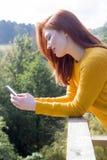 Usando el teléfono elegante en jardín Foto de archivo