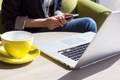 Usando el teléfono móvil y el ordenador portátil en café Imágenes de archivo libres de regalías