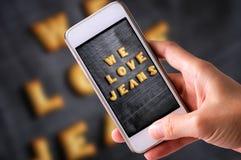 Usando el teléfono móvil para tomar las fotos de las galletas ABC bajo la forma de palabra AMAMOS fondo de la mezclilla del alfab Imagen de archivo libre de regalías