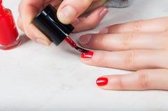 Usando a escova do aplicador para aplicar o polimento do vermelho à unha, auto m Fotos de Stock Royalty Free