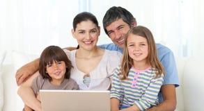 usando felice del sofà del computer portatile della famiglia Immagine Stock