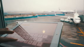 Usando la almohadilla táctil por la ventana en el aeropuerto almacen de metraje de vídeo