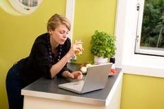 Usando la computadora portátil en cocina Imagenes de archivo