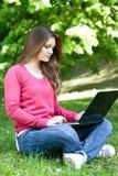 Usando la computadora portátil en el parque Imágenes de archivo libres de regalías