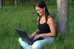 Usando la computadora portátil en el parque Foto de archivo libre de regalías