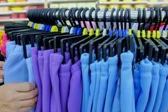 Usando la mano para elegir un sistema de ropa lleve por color y clasifique fotos de archivo
