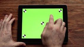 Usando la tableta con la pantalla verde en la tabla de madera Tirado en 4k, uhd almacen de metraje de vídeo