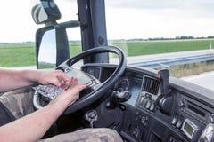 Usando las píldoras mientras que conduce el camión Foto de archivo libre de regalías