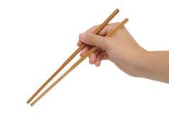 Usando los palillos de bambú con la mano Foto de archivo