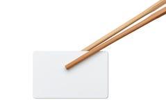Usando los palillos para sostener una tarjeta vacía Imagen de archivo libre de regalías