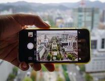 Usando móvil al paisaje urbano del cature Imagen de archivo
