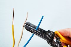 Usando o cortador do descascador de fios durante o installati prender elétrico imagem de stock