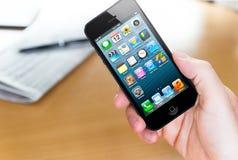 Usando o iphone 5 de Apple Fotografia de Stock