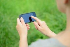 Usando o iPhone de Apple Imagens de Stock Royalty Free