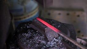 Usando o martelo pneumático para dar forma ao metal quente filme