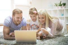Usando o portátil Família em casa foto de stock royalty free