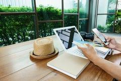 Usando o telefone celular e o portátil na tabela de madeira Fotografia de Stock