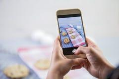Usando o telefone celular para fotografar o alimento Fotos do alimento para meios sociais fotografia de stock