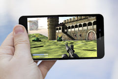 Usando o telefone celular para jogar Fotografia de Stock Royalty Free