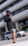 Usando o telefone móvel em uma rua fotografia de stock royalty free