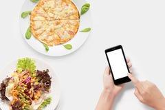 Usando smartphone con la pizza, sistema de la ensalada aislado aislado en pizca Foto de archivo