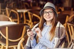 Usando Smartphone en café de la calle imágenes de archivo libres de regalías