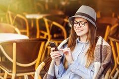 Usando Smartphone en café de la calle imagenes de archivo