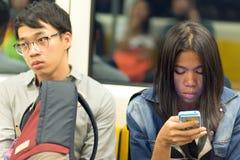 Usando smartphone en el transporte público Foto de archivo libre de regalías