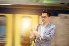 Usando smartphone en la estación de tren Fotografía de archivo