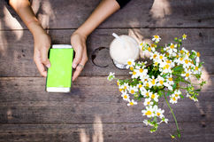 Usando smartphone encima de la tabla de madera Imagenes de archivo