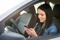 Usando smartphone mientras que conduce Imagen de archivo libre de regalías