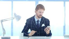 Usando Smartphone para leer envía por correo electrónico mensajes del nad, sirven con los pelos rojos fotos de archivo