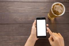 Usando smartphone por otra parte de la cerveza en el pub Fotos de archivo