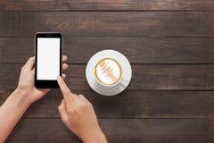 Usando smartphone por otra parte del café en la tabla de madera Fotografía de archivo libre de regalías