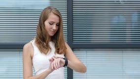 Usando Smartwatch de la muchacha hermosa, oficina exterior almacen de metraje de vídeo