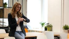 Usando Smartwatch, mujer de negocios que se sienta en el escritorio en oficina almacen de video