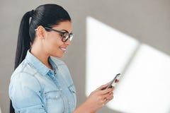 Usando su teléfono elegante con placer Imagen de archivo