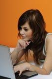 usando sveglio del computer portatile della ragazza del brunette della base Fotografie Stock