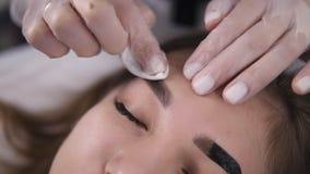 Usando um disco limpo branco do algodão para remover a pintura das testas Uma mulher coloca na cama durante uma visita na beleza video estoque