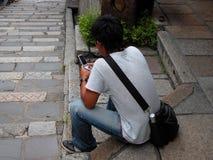 Usando um handyphone Foto de Stock Royalty Free