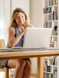 Usando um portátil em casa imagem de stock royalty free