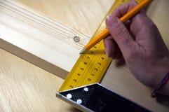 Usando um quadrado para medir uma madeira de pinho Foto de Stock Royalty Free