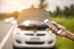Usando uma chamada de telefone celular um mecânico de carro porque o carro era quebrado Imagens de Stock Royalty Free