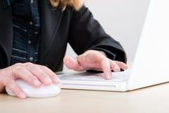 Usando un computer portatile e un mouse fotografia stock