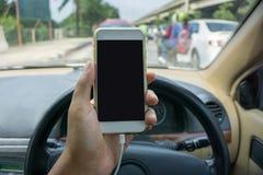 Usando un smartphone mientras que conduce un coche Imagen de archivo
