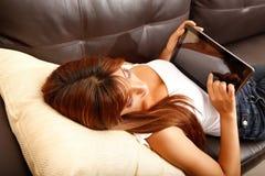 Usando un Tablet PC en el sofá Fotografía de archivo