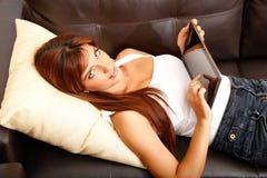 Usando un Tablet PC en el sofá Imagen de archivo libre de regalías