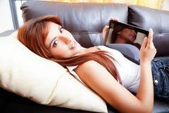 Usando un Tablet PC en el sofá Fotos de archivo libres de regalías