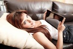 Usando un Tablet PC en el sofá Imagenes de archivo